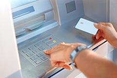 Mano de una mujer con una tarjeta de crédito, usando una atmósfera Mujer que usa una máquina de la atmósfera con su tarjeta de cr foto de archivo libre de regalías