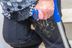 mano de una mujer discapacitada mayor que sostiene una muleta Imagenes de archivo