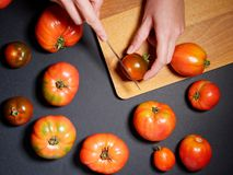 Mano de una mujer joven que corta el tomate fresco Visión superior Foto de archivo