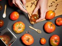 Mano de una mujer joven que corta el tomate fresco Visión superior Fotografía de archivo