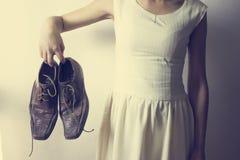 Mano de una mujer que sostiene los zapatos para los hombres Fotografía de archivo libre de regalías
