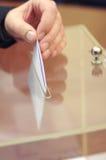 Mano de una persona que pone una votación en la caja de votación Imagen de archivo libre de regalías