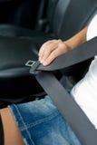 Mano de Womans con el cinturón de seguridad en el coche Fotos de archivo libres de regalías