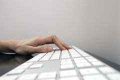 Mano de Womans en pulsar blanco plano del teclado Imágenes de archivo libres de regalías