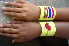 Mano dei bambini con il wristband della Tailandia Fotografia Stock