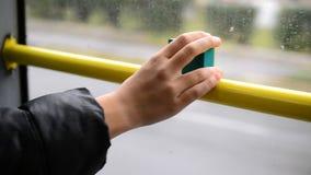 Mano del adolescente que sostiene una cámara de la acción cerca de ventana en autobús almacen de video