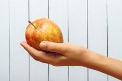 Mano del adolescente que sostiene una manzana en fondo de madera Vista lateral Copie el espacio Fotos de archivo