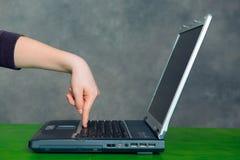 Mano del adolescente usando el ordenador portátil Fotos de archivo