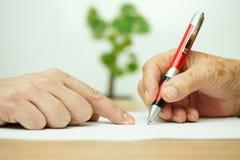 Mano del adulto joven que señala a la persona mayor donde firmar Imagen de archivo