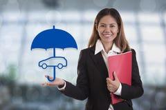 Mano del agente del vendedor que sostiene el coche de la protección del paraguas foto de archivo