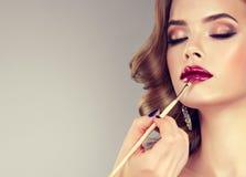 Mano del amo del maquillaje, labios de pintura del modelo fotos de archivo