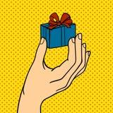 Mano del arte pop con el ejemplo del vector de la caja de regalo Imagenes de archivo