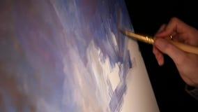 Mano del artista con la brocha que pinta la imagen metrajes