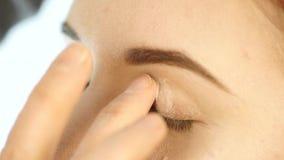 Mano del artista de maquillaje del primer, aplicando el sombreador de ojos al ojo del ` s de la mujer usando los fingeres almacen de video
