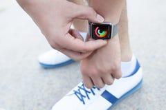 Mano del atleta con el reloj de Apple y actividad del app en la pantalla Imagen de archivo libre de regalías