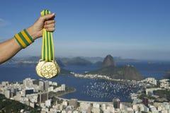 Mano del atleta Holding Gold Medals Rio Skyline Imagenes de archivo
