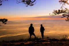 Mano del aumento del hombre de la remolque de Silluate ascendente y situación durante puesta del sol en el top imagen de archivo libre de regalías