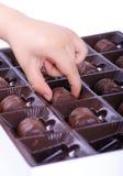 Mano del bambino che cattura un cioccolato Fotografia Stock Libera da Diritti