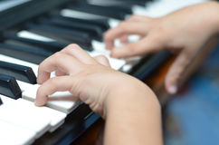 Mano del bambino che gioca il primo piano della tastiera Fotografie Stock Libere da Diritti