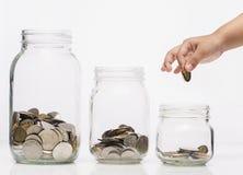 Mano del bambino che mette una moneta nella bottiglia di vetro, concetto futuro di risparmio Immagine Stock