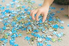 Mano del bambino che prende il pezzo di puzzle Immagine Stock