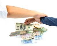 Mano del bambino che seleziona la fermata americana della banconota del dollaro dalla mano dell'uomo Immagini Stock Libere da Diritti
