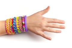 Mano del bambino con i braccialetti di gomma variopinti del telaio dell'arcobaleno Fotografie Stock