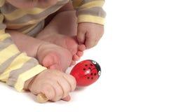 Mano del bambino con il giocattolo rosso Immagini Stock
