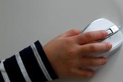 Mano del bambino con il topo del computer sulla Tabella bianca fotografie stock libere da diritti