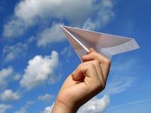 Mano del bambino con l'aereo di carta fotografie stock