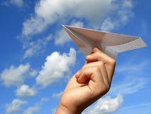 Mano del bambino con l'aereo di carta fotografie stock libere da diritti