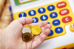 Mano del bambino con le monete ed il registratore di cassa del giocattolo Fotografia Stock