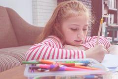 Mano del bambino facendo uso della matita da praticare scrivere su un libro Immagini Stock Libere da Diritti