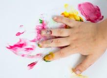 Mano del bambino mentre fanno fingerpaint Fotografia Stock