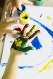 Mano del bambino mentre fanno fingerpaint immagini stock libere da diritti
