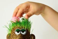 Mano del bambino piccolo che tiene due uova di Pasqua sulla figura della vermiculite con la testa erbosa Fotografia Stock Libera da Diritti