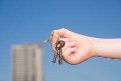 Mano del bambino tenendo le vecchie chiavi alla casa contro il cielo Immagine Stock