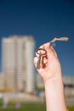 Mano del bambino tenendo le vecchie chiavi alla casa contro il cielo Fotografia Stock