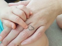 Mano del bebé con la mano de la mamá fotos de archivo