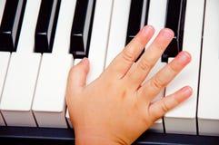 Mano del bebé en piano Fotografía de archivo