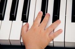 Mano del bebé en piano Fotos de archivo