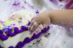 Mano del bebé en torta Foto de archivo