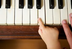 Mano del bebé que juega el piano con la mano adulta Foto de archivo libre de regalías