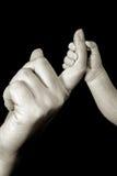 mano del bebé que se sostiene por la momia Imagenes de archivo