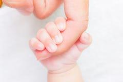 Mano del bebé que sostiene el finger adulto Fotos de archivo