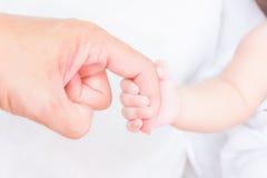 Mano del bebé que sostiene el finger adulto Foto de archivo