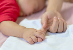 Mano del bebé que sostiene suavemente el finger de la mamá Imágenes de archivo libres de regalías