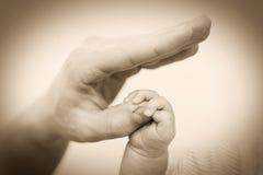 Mano del bebé que sostiene suavemente el finger del adulto Foto de archivo libre de regalías