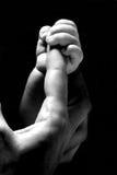 Mano del bebé que sostiene un dedo fotografía de archivo libre de regalías