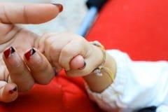 Mano del bebé y cierre de la mano de la madre para arriba: concepto de amor y de familia Fotos de archivo libres de regalías